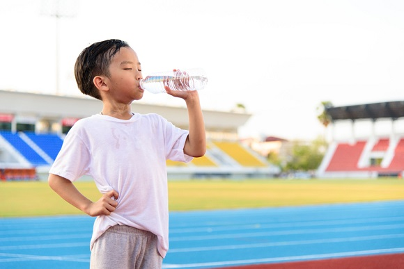 Young Asian boy drinking fresh water from plastic bottle after sport in stadium.; Shutterstock ID 338393024